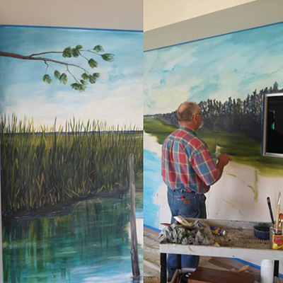 A painter working on the mural inside of the office lobby